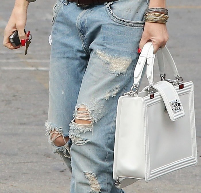 Gwen Stefani keeping her accessories simple — a geometric white purse and a stack of bangles