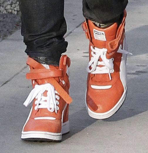 Gwen's orange wedge sneakers from Puma adding color to her ensemble