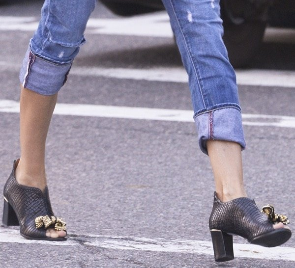 Sarah Jessica Parker wearing shoes featuring an allover reptilian embossing with thick heels and gold bow detail above the peep toes