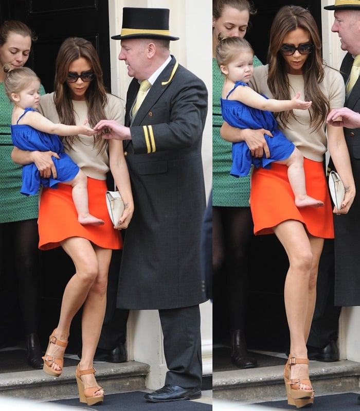 Victoria Beckham wore a cheery orange skirt and a nude top with her rich leather sandals