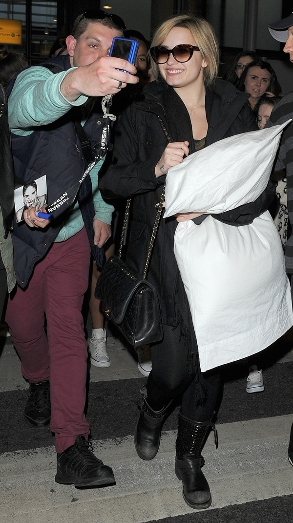 Demi Lovato greeting fans as she arrives at Heathrow Airport in London