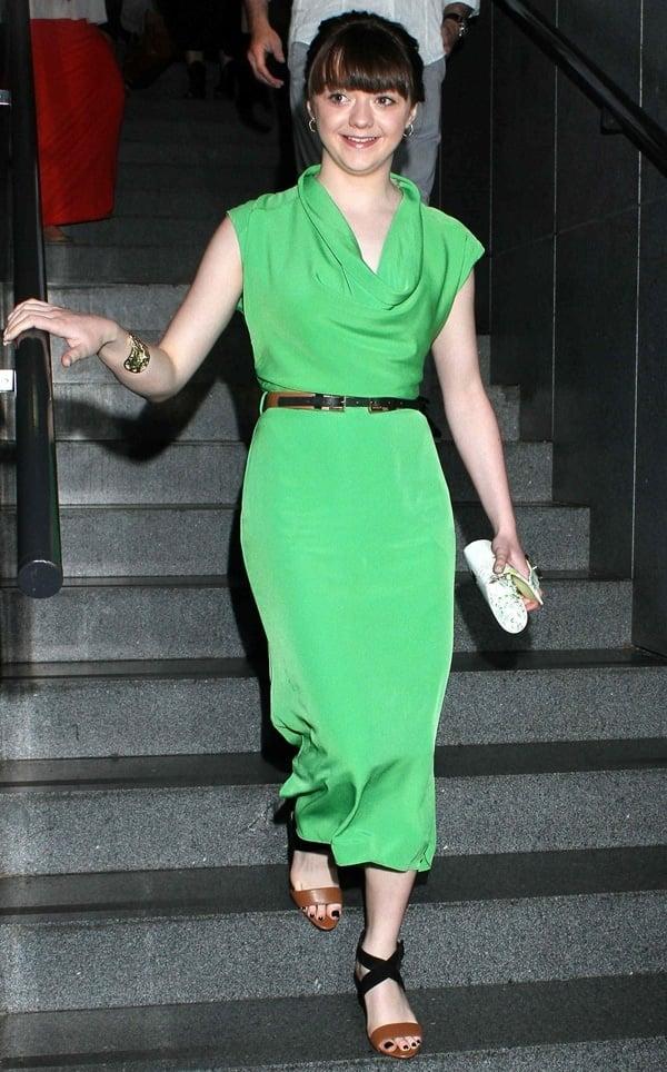 Maisie Williams wearinga green cowl neck dress