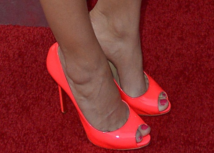 Camilla Belle's feet in neon coral Christian Louboutin pumps