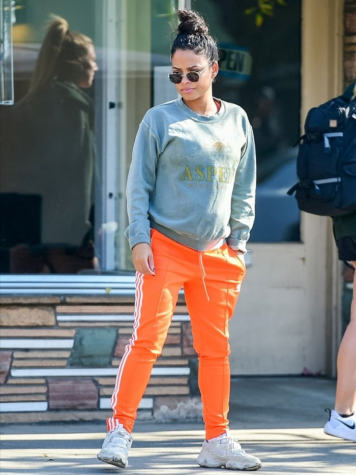 Christina Milian, an American actress/singer/songwriter of Cuban origin, dressed casually wearing a sweatshirt and orange pants