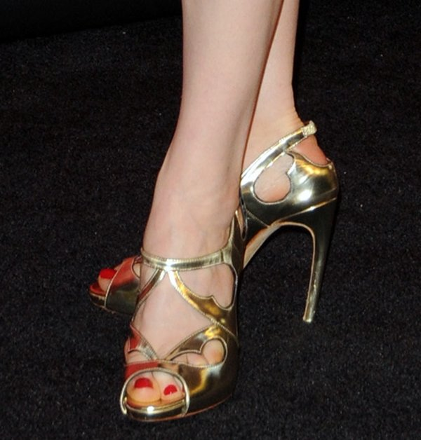 Ellie Kemper's red pedicure peeks out from her gold Rupert Sanderson sandals