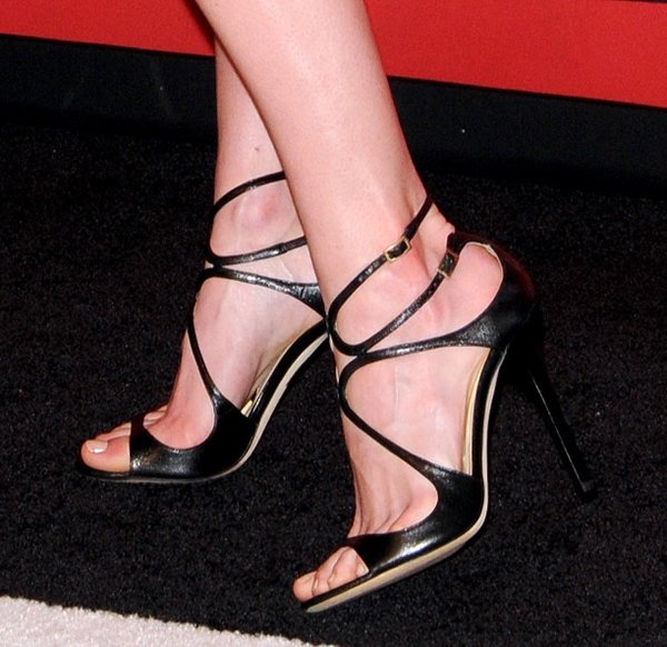 Hilary Rhoda turns her foot sideways in a pair of Jimmy Choo sandals