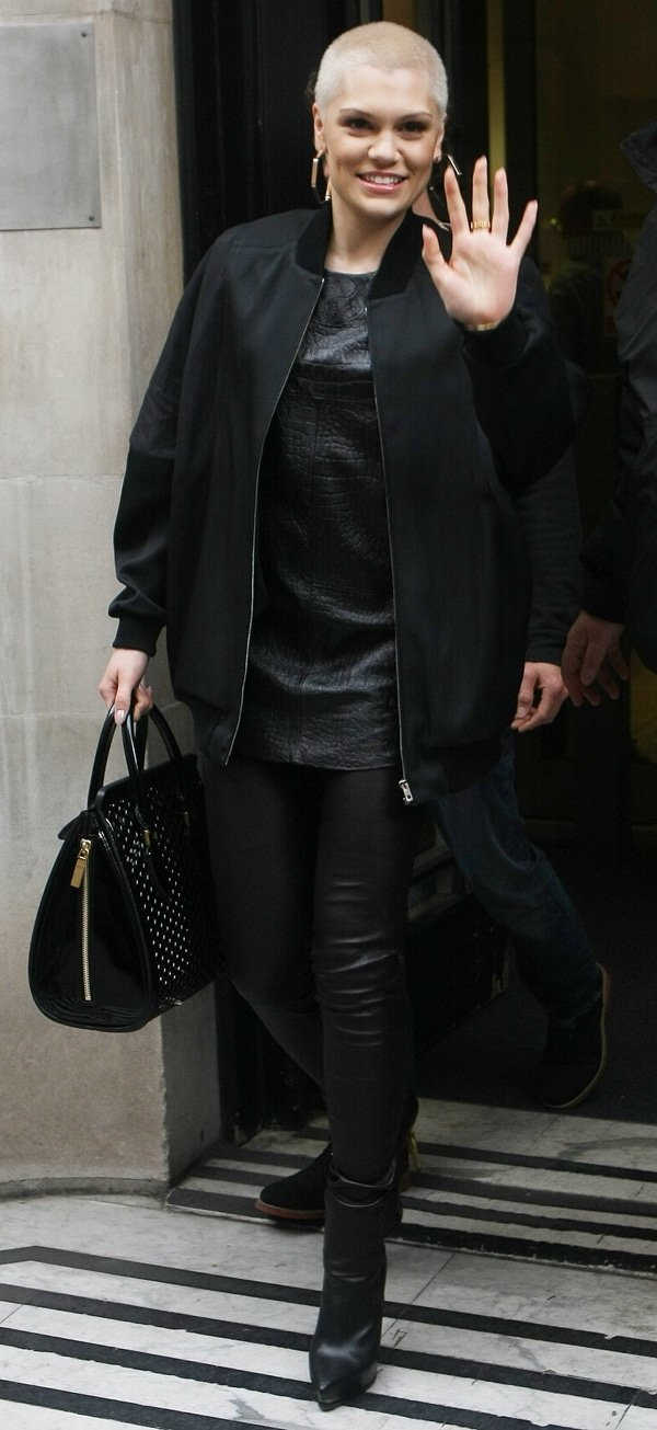 Jessie J rocking tight leather pants, a textured top, and a varsity jacket