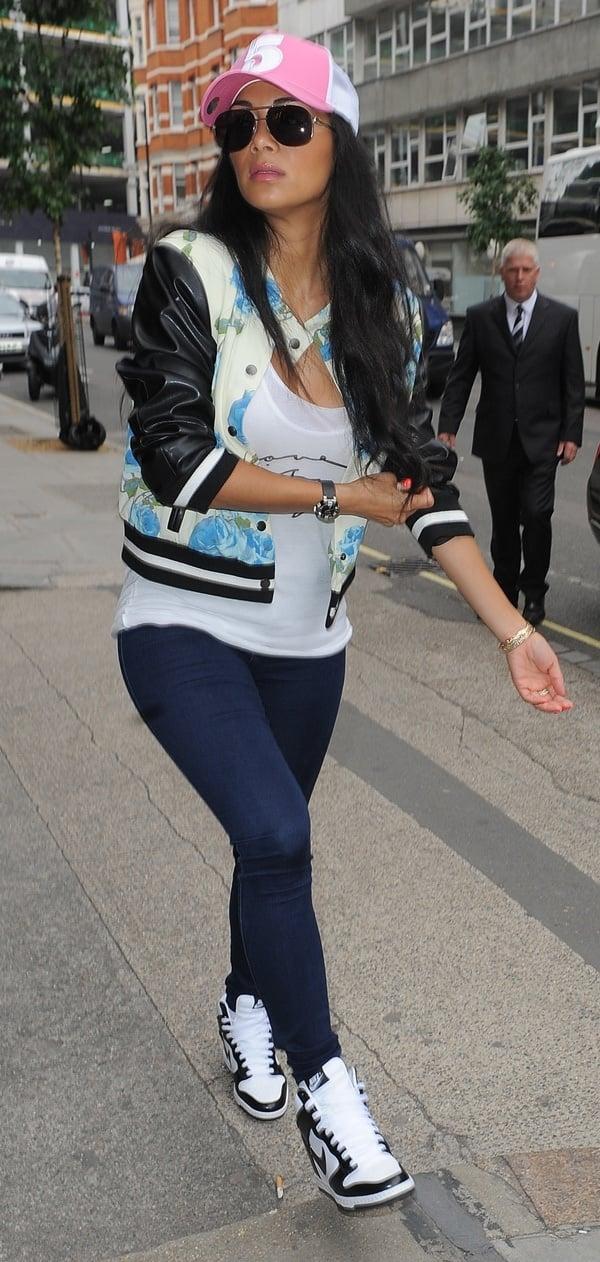 01e8db80cd8 Nicole Scherzinger accessorized with a pink baseball cap and aviator  sunglasses