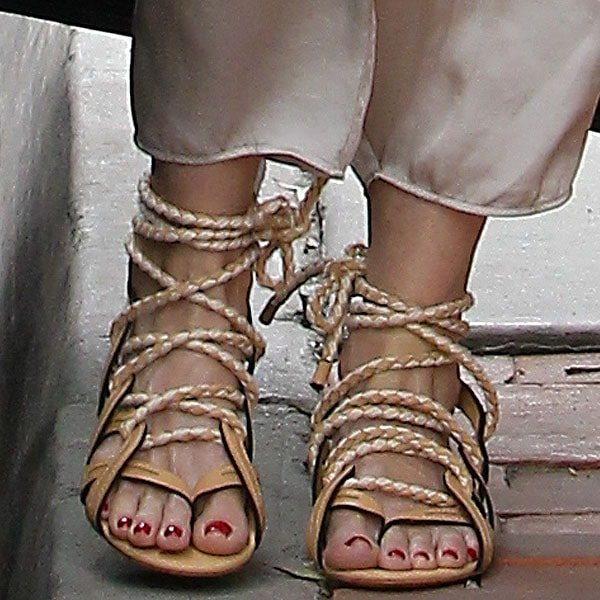 The American singer and songwriter showing off her feet in tan lace-up flat sandals