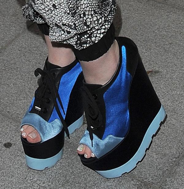 Iggy Azalea in wedge sneakersmade of glazed nylon
