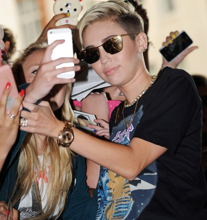 Miley Cyrus poses for photographs with fans outside the BBC Radio 1 studios in London, England, on July 18, 2013