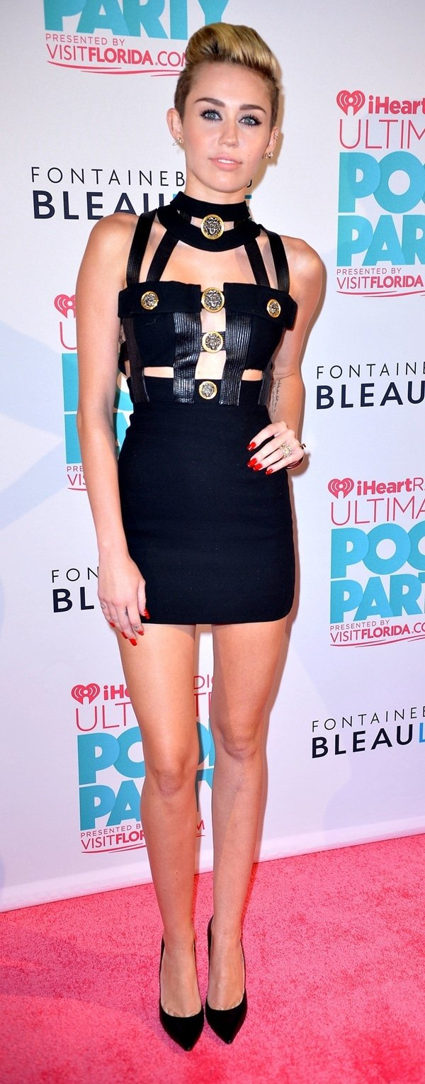 Miley Cyrus shows off her coin-embellished Versace bondage minidress on the red carpet