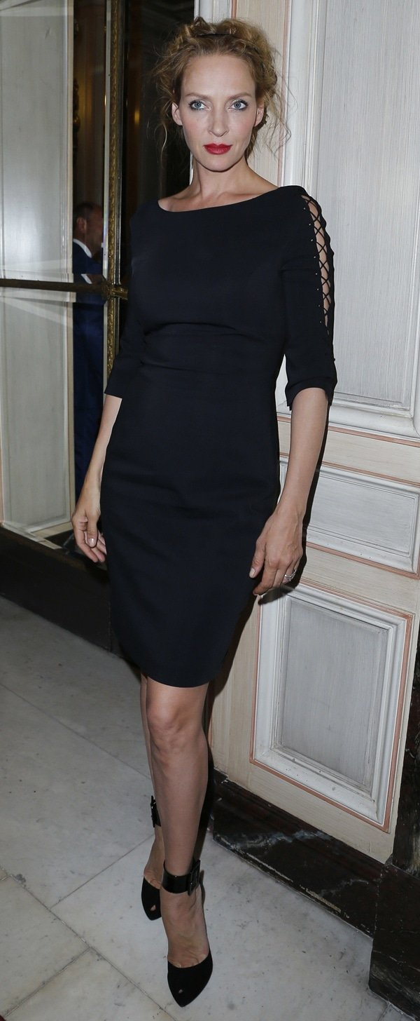 Uma Thurman flaunts her sexy legs in a black dress with lace-up sleeves