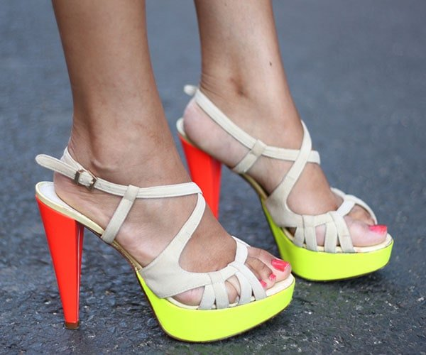Holy Rakoto in striking summery shoes with bright neon yellow platforms and bright orange heels