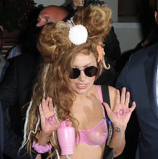 Lady Gaga's hair was adorned with a sea shell, a starfish, and a sea lion, and she was seen carrying a plastic pink bottle with the words ART and POP scribbled in pink letters on each of her hands