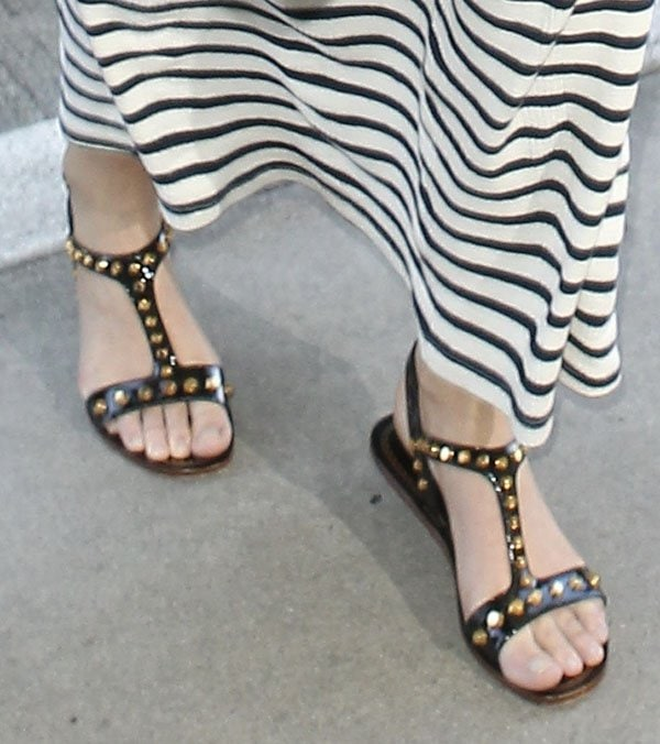 Miranda Kerr wearing Prada sandals featuring patent ankle straps and t-straps that are embellished with brass-toned studs