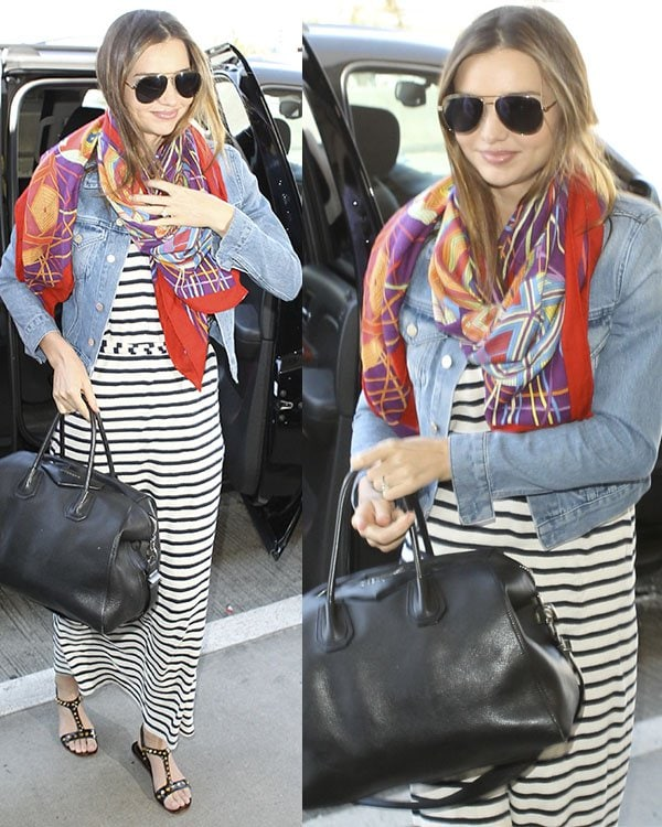 Miranda Kerr arrives at LAX airport a striped maxi dress, a cropped denim jacket, a colorful scarf, and a pair of studded black sandal flats