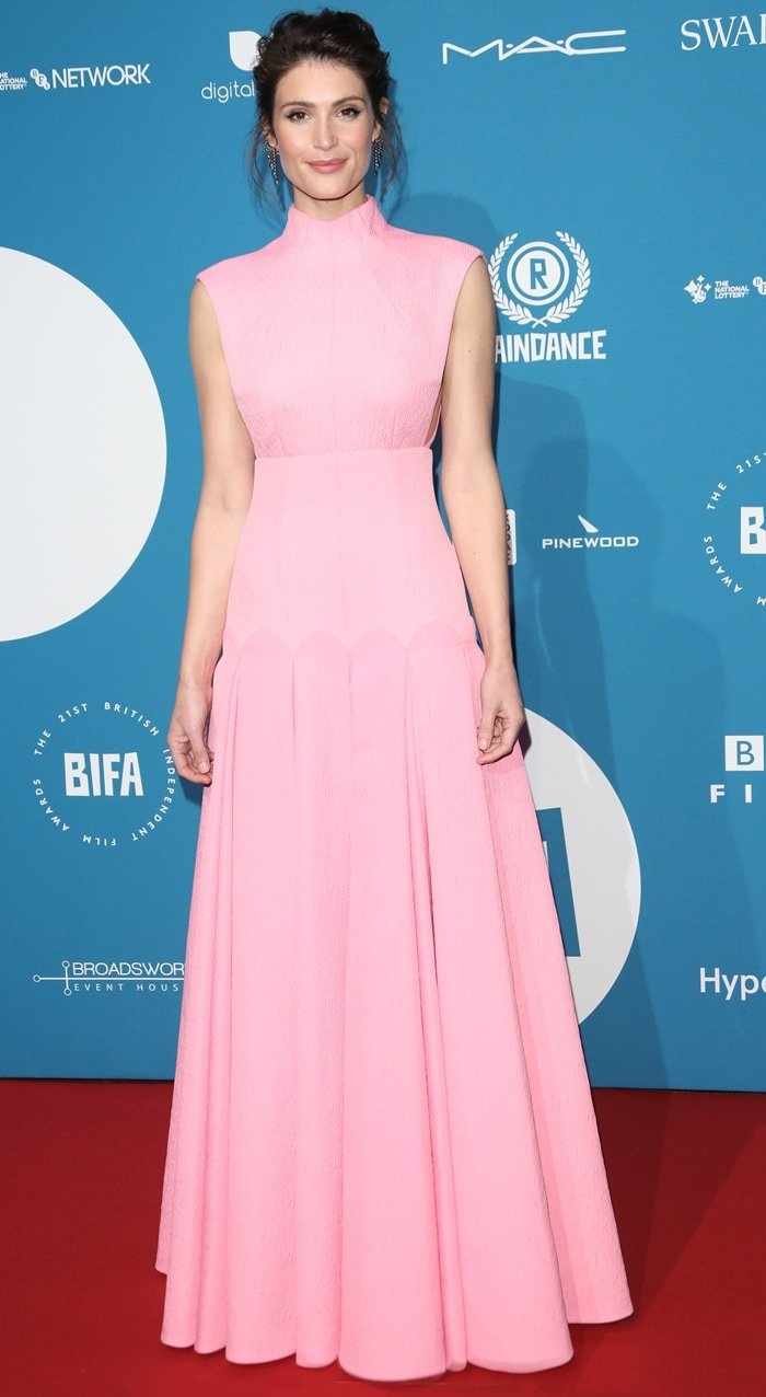 Gemma Arterton wearing an Emília Wickstead dress, Giuseppe Zanotti shoes, a Jimmy Choo bag, and Jessica McCormack earrings at the 2018 British Independent Film Awards