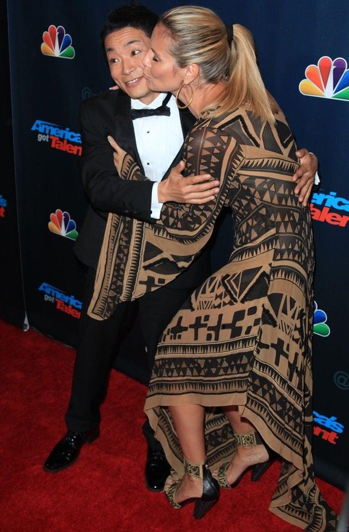 Kenichi Ebina, the winner of the eighth season of America's Got Talent, gets a kiss from Heidi Klum