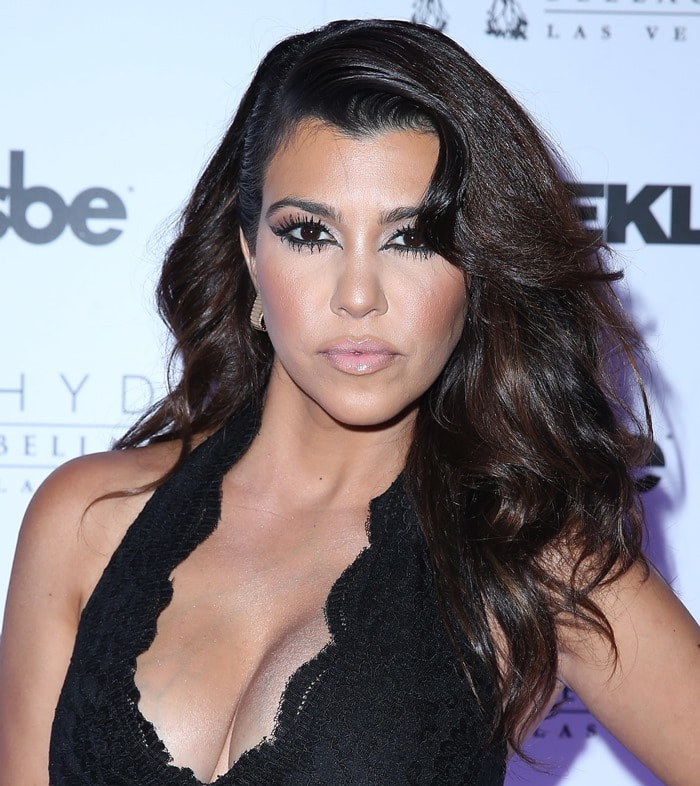 Kourtney Kardashian wearing a lace-trimmed jumpsuit with a plunging neckline