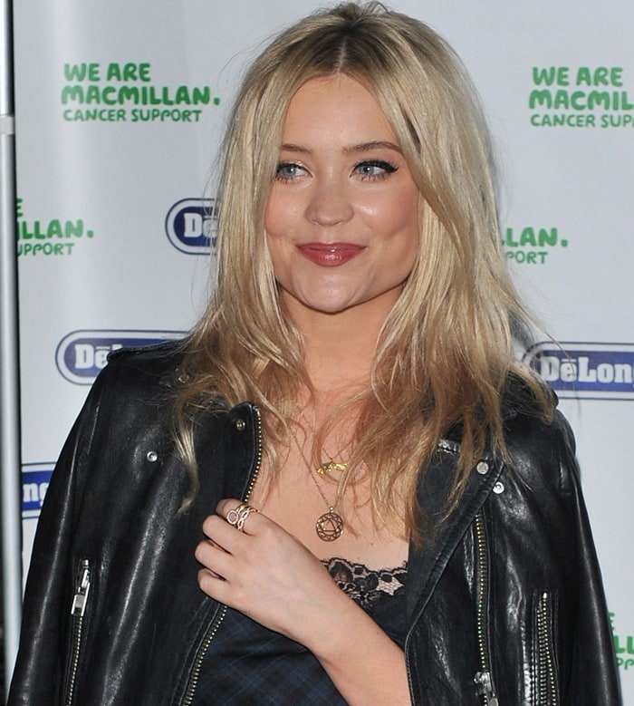 Laura Whitmore grins for a photo as her blonde waves cascade around her shoulders