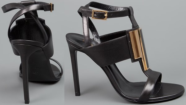 """Black Saint Laurent """"Janis"""" sandals with thick t-straps in front, a gold plaque detail, wrap-around ankle straps, and leather-covered stiletto heels"""