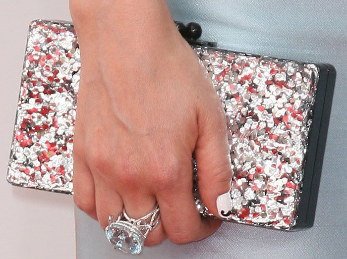 Zooey Deschanel shows off her Chanel cocktail ring — and her quirky mustache-manicure — while holding her Edie Parker clutch