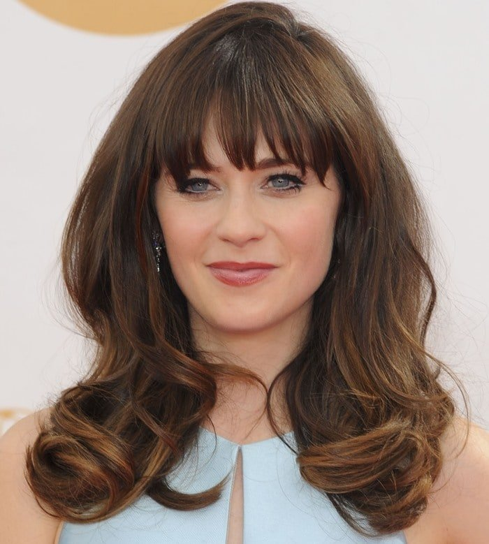 Zooey Deschanel wears her brown hair down and curled at the Emmy Awards