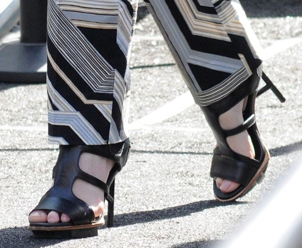 Coco Rocha channeling a more masculine style and pairing them with strappy sandals as she heads to a fashion show during 2014 Mercedes-Benz Fashion Week in New York City on September 9, 2013