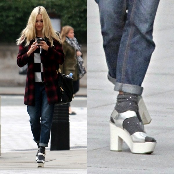 Fearne Cotton arriving at the BBC Radio 1 studios in a red-and-black coat, a black-and-white sweater, loose-fitting jeans, and silver platform sandals in London, United Kingdom, on September 24, 2013