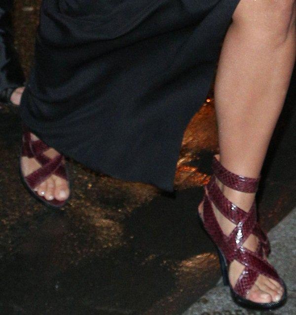 Kim Kardashian showing off her feet in glazed and strappy snakeskin sandals