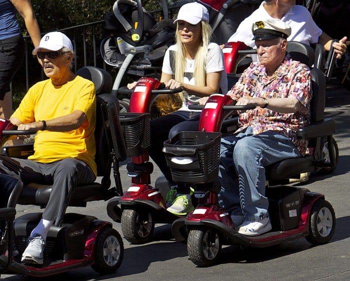 Hugh Hefner and Crystal Hefner ride mobility scooters through Disneyland Park