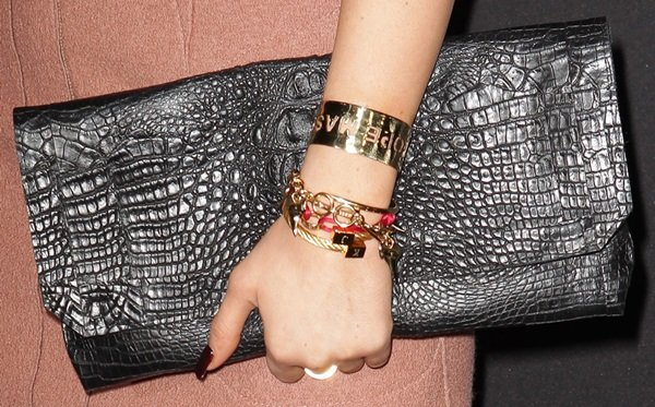 Kylie Jenner holds a metallic clutch and shows off her stack of bracelets
