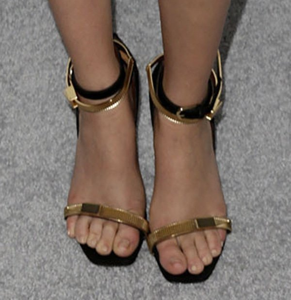 Zoey Deutch wearing black and gold heels