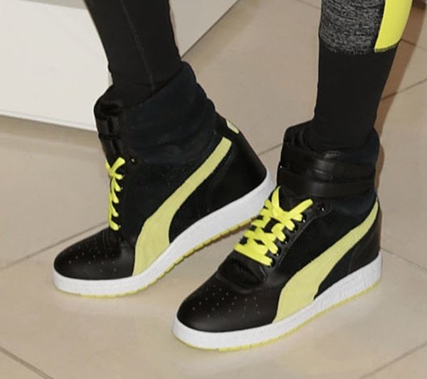 Alessandra Ambrosio wears a pair of Puma wedge sneakers during a Victoria's Secret promotion