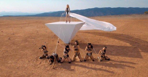 Britney Spears wearing tasseled ankle-strap heels for a bondage scene in the desert