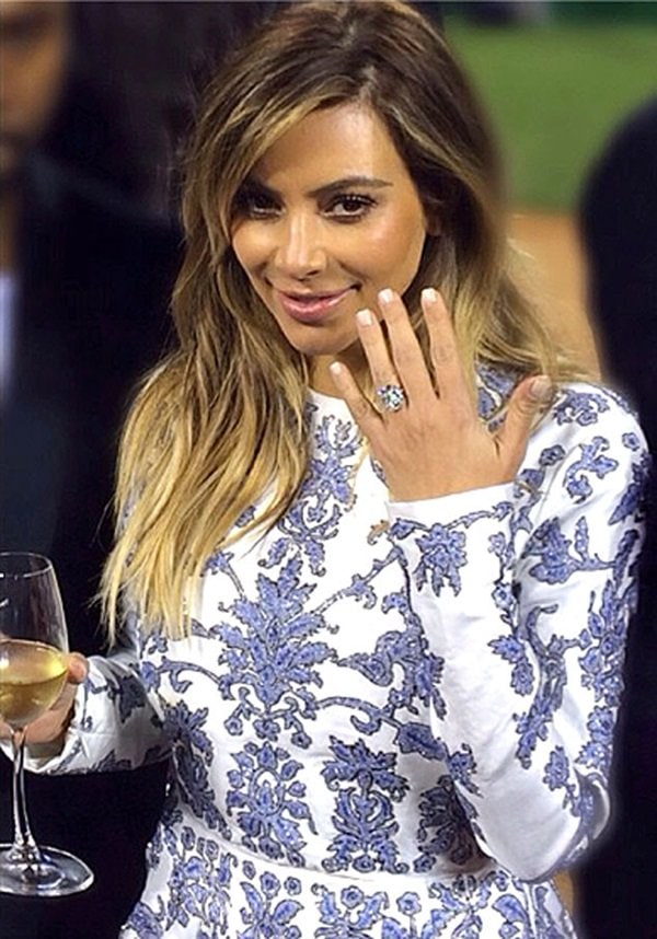 Kim Kardashian's engagement ring features a 15 carat cushion cut diamond in a prong setting and a diamond paved band