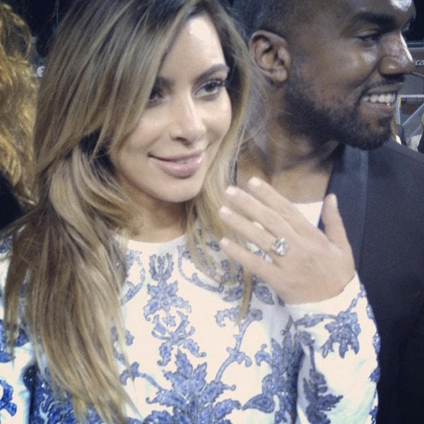 Kim Kardashian looking happy and glowing as she shows off her ring in a printed Valentino Fall 2013 dress