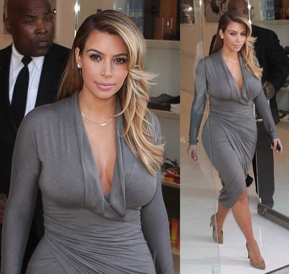 Kim Kardashian flaunting her curves in a fitted gray long-sleeved wrap dress with a plunging neckline