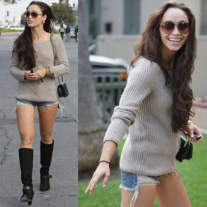 Cara Santana pairs black knee-high boots with ripped daisy duke shorts