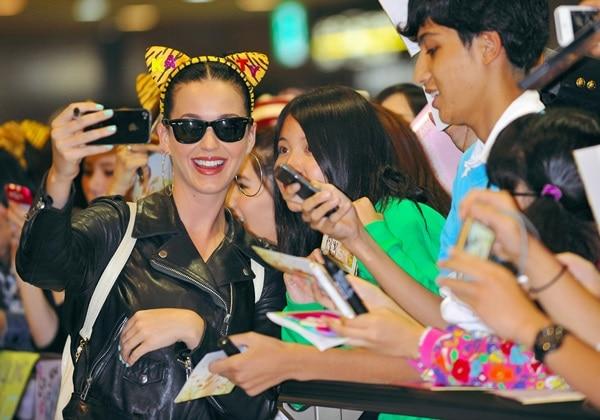 Katy Perry greets fans as she arrives at Narita International Airport