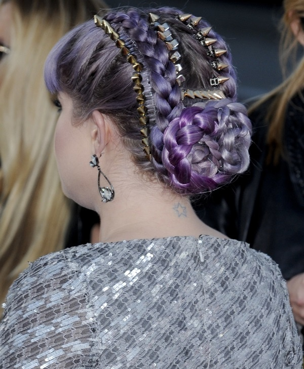 Kelly shows off her neck tattoo by wearing her lavender hair up in a braided and studded updo