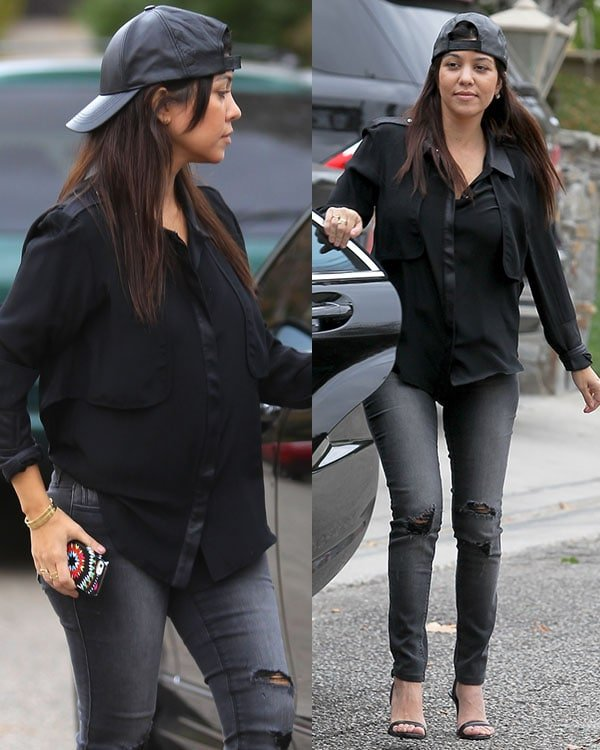 Kourtney Kardashian paired a loose collared, long-sleeved shirt in black with ripped dark-washed denims and styled with a baseball cap worn backward