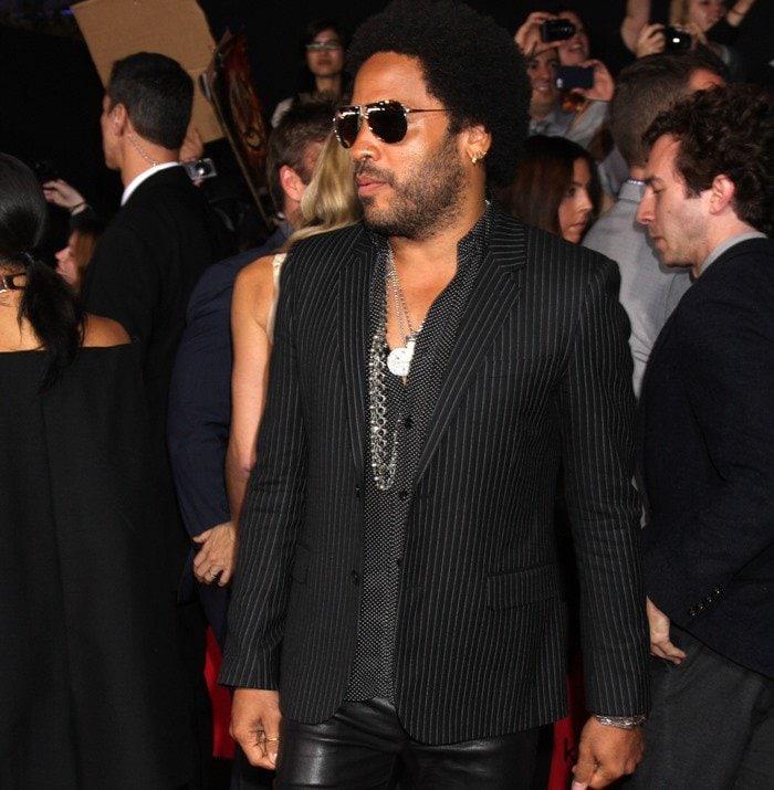 Lenny Kravitz wears a pinstripe jacket and dark aviators on the red carpet