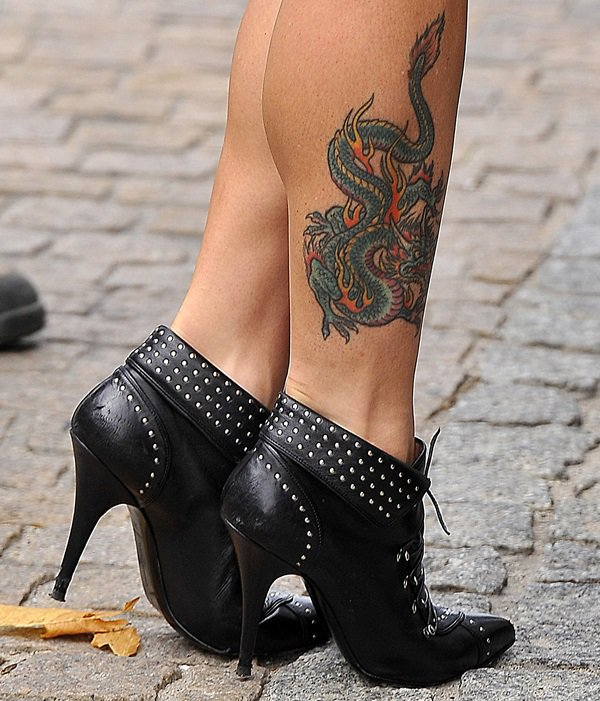 Mel C showing off the colorful, ornate dragon tattoo on her right leg