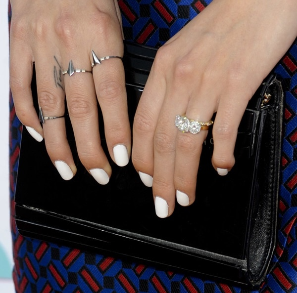 Nikki Reed shows off her Paul finger tattoo while holding a Jimmy Choo clutch