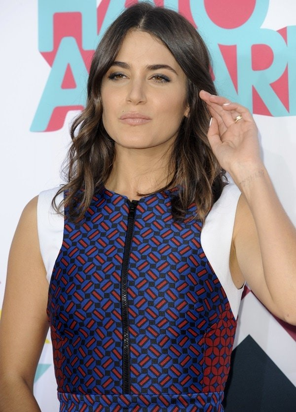Nikki Reed brushes her hair out of her face while posing for photos at the TeenNick HALO Awards