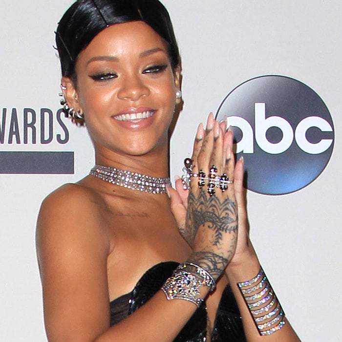 Rihanna shows off her ample diamond jewelry and hand tattoos at the AMAs
