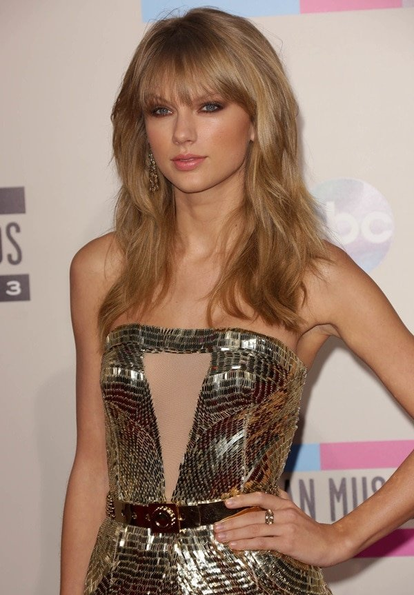 Taylor dressed up in a gold Julien Macdonald Fall 2013 mini-dress that offered plenty of sex appeal