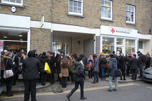 A line of shoppers stands outside the British Red Cross